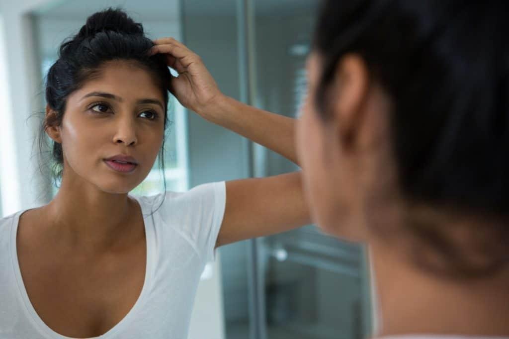 Pretty woman reflecting on mirror